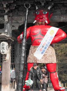 仁王立ちする高さ4メートルの巨大な赤鬼。厄払いに参拝客が足の間をくぐる=揖斐川町谷汲徳積で