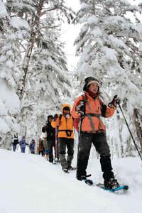 スノーシューを履いて雪上トレッキングを楽しむ参加者たち=高山市高根町のチャオ御岳スノーリゾートで