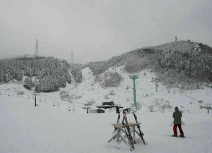 ゲレンデの向こうで霧に覆われる鉢伏山。山の右手の北側の尾根に風車が設置される=南越前町の今庄365スキー場で