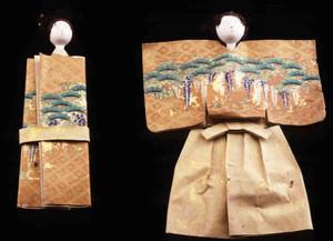 丸顔の頭に紙の衣装をまとう「立雛」=彦根城博物館で