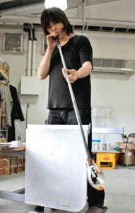 ガラス玉を吹いて形を作る湊秀樹さん=大津市の障害者福祉サービス事業所「おおぎの里」で