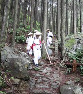 巡礼姿で石畳を踏みしめる参加者ら=紀北町紀伊長島区のツヅラト峠登り口付近で