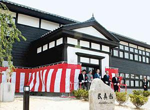 開館した民具館。学びやを象徴する二宮金次郎像(左)も建つ=砺波市太郎丸で
