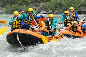 呼吸を合わせパドルをこぎ天竜川を下る参加者たち=飯田市で