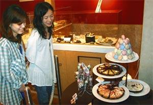 マカロンやケーキそっくりの楽しいスイーツ石けんに見入る来館者=磐田市香りの博物館で