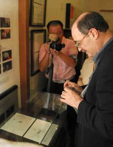 感慨深げな表情で父親の「命のビザ」のコピーを写真撮影するチャールズ・マンスキーさん(右)=敦賀市金ケ崎町の「人道の港敦賀ムゼウム」で