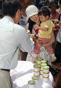 小口利幸塩尻市長(左)から新発売のレタスアイスクリームを受け取る来場者=塩尻市北小野のチロルの森で