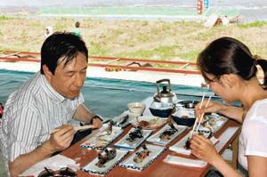 川沿いの座敷で、アユ料理に舌鼓を打つ観光客=揖斐川町で