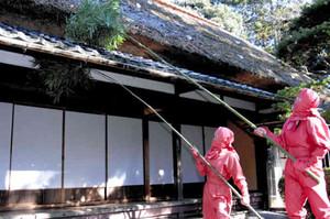 かやぶき屋根のほこりを落とす忍者姿の職員=伊賀市の伊賀流忍者博物館で