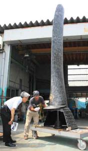 高さ4メートルの前田利長公銀鯰尾形兜の像を見学する高橋市長(左)=高岡市長江のモメンタムファクトリー・Oriiで