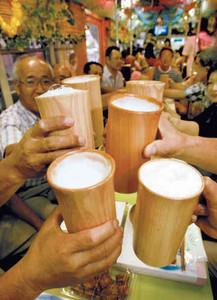 ヒノキの木製ジョッキでクリーミーな泡立ちの生ビールを楽しむ人たち=豊橋市内で