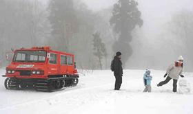 雪上車から降りて遊ぶ家族連れ=野沢温泉スキー場で