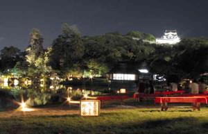 ライトアップされた彦根城天守を望みながら、幻想的な園内の雰囲気を楽しむ来場者ら=彦根市の玄宮園で