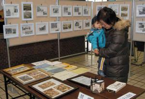 藤森真輝登さん提供の懐かしい写真に見入る来庁者=諏訪市役所で