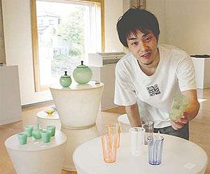 色とりどりのガラス作品と新人スタッフの森さん=富山市古沢の富山ガラス工房で