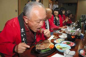 牛のステーキを食べる参加者=穴水町川島の料理旅館竹亭で