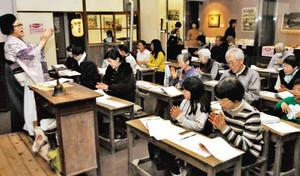 再現された昭和10年代の教室で音楽家・中村和子さん(左)と歌を歌う親子連れら