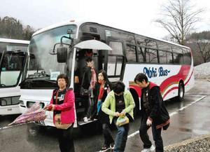 白川郷に降り立つ定期観光バスの利用者=白川村で