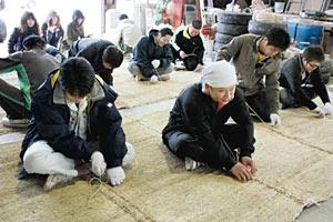 青柏祭に向けてむしろを編む若衆ら=七尾市佐味町で