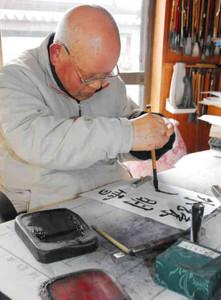 利き手と逆の左手で筆を握り、右手を添えながら字をしたためる田沢豊和さん=可児市緑ケ丘で