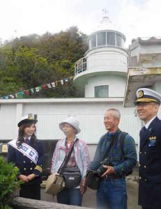 神島灯台を案内する一日灯台長の水谷さん(左)=鳥羽市沖の神島で