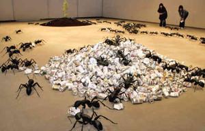 空き缶の山から木の山へと逃げ出すアリの模型を展示し、環境破壊への批判を込めた深田さんの作品=守山市民ホールで