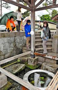 観光ボランティアガイド(中央)の説明で名水巡りを楽しむ参加者たち=大野市泉町の御清水で