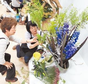 「中日いけばな芸術展」の開幕を控え、生け込み作業をする出瓶者ら=1日、浜松市中区の遠鉄百貨店で(川戸賢一撮影)