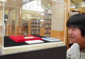 1万3千年前の土偶に見入る来館者=東近江市の永源寺図書館で