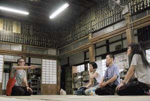 集まった作家たちに寺について説明する住職の今井さん(左)=金沢市瓢箪町で