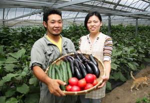 農園で採れたトマトなどを抱える北川さんと婚約者=多気町丹生で