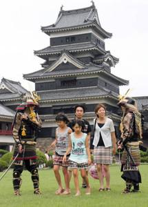 天守閣を前に観光客をもてなす甲冑姿の学生ら=松本市の国宝松本城で