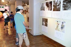 広島、長崎の原爆の惨状を伝える写真パネルに見入る市民ら=島田市のプラザおおるりで