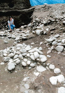 溝の側面や底面に自然石が並べられた遺構=多気町の相可出張遺跡で