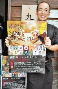 南信州酒メッセ2010のポスターを持ち、来場を呼び掛ける笹原良祐さん=飯田市で