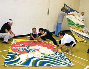 最終作業で大凧の重心を決める住民ら=白山市郷公民館で