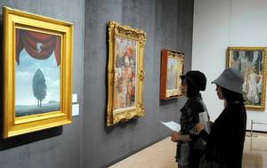 初公開されたマグリットの油絵「星座」(左)に見入る女性ら=小牧市小牧のメナード美術館で