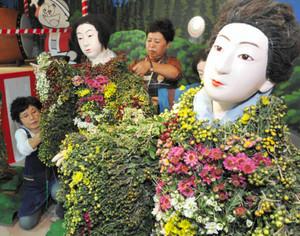 色とりどりの花が丁寧に飾り付けられていく菊人形=飯田市の元善光寺で