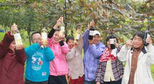 ワインフェスタで出すワインを掲げるピア名古屋の通所者=多治見市緑ケ丘の神言会多治見修道院で