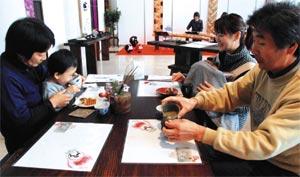 琴の音色が響く中、県産緑茶と洋菓子を堪能する来場者=静岡市駿河区のグランシップで