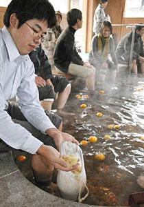 ユズのほか、ユズの中身を入れた袋が漬けられた足湯=輪島市河井町で