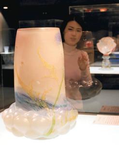ガレ作「あざみ文花器」について説明する小林宏子学芸員。右奥は「花器フランスの薔薇」=諏訪市で
