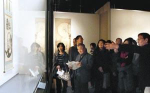 白隠慧鶴の墨画「達磨図」について、飯田真学芸課長(右)の説明を聞く参加者=静岡市駿河区の県立美術館で
