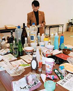 会場に並べられた菓子の空き袋や瓶などの漂着物=氷見市海浜植物園で