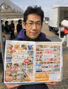 設営の進む会場で、ポスターを手に来場を呼びかける安藤代表理事=土岐市土岐ケ丘の土岐プラズマリサーチパークで