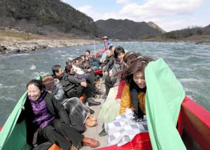 船の傾きと水しぶきに歓声を上げながら川下りを楽しむ乗客=岐阜・愛知県境の木曽川で