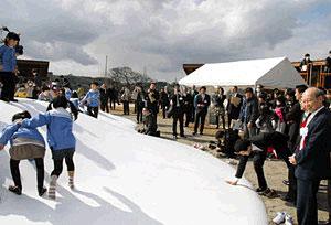 石井知事(右)らが見守る中、見晴らしの丘で遊ぶ子どもたち=富岩運河環水公園で