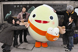 観光客とふれ合うわくたまくん=七尾市和倉町で