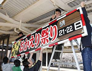 ホームの天井におかえり祭りの看板を取り付ける美川商工会青年部員=JR美川駅で