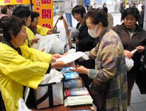 コウナゴが入った袋を手渡す篠島女将会の女性ら(左)=名古屋市中区の名鉄金山駅で